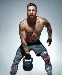 Sporty man doing exercises with kettlebell. Photo of man with naked torso on grey background. Strength and motivation