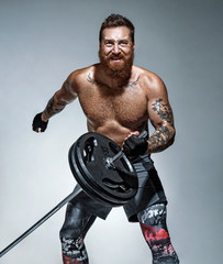 Strong man does landmine exercises, workout with barbell. Photo of sporty man on grey background. Strength and motivation