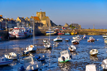 Port at low tide at the end of the sunny day and church of Saint-Nicolas of Barfleur, a commune in the peninsula of Cotentin in the Manche department in Lower Normandy in north-western France