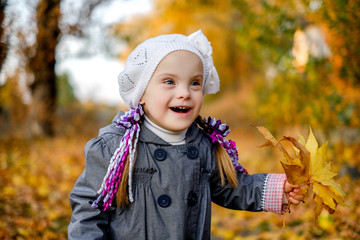 Down syndrome schild smiling in autumn forest, happy despite all problems, awareness