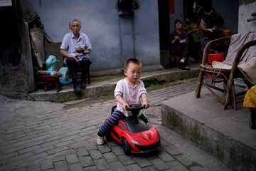 A child rides a toy car at an old residential compound in Wuhan