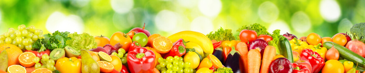 Wall Mural - Isolated on green blurred background fruits and vegetables.