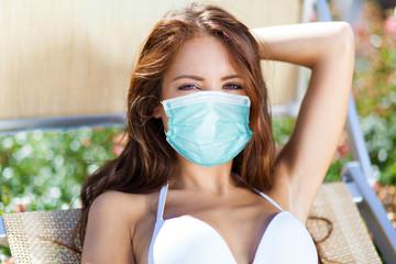 Beautiful woman sunbathing by the pool wearing a mask, coronavirus concept
