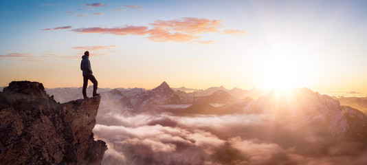 Magical Fantasy Adventure Composite of Man Hiking on top of a rocky mountain peak. Background Landscape from British Columbia, Canada. Sunset or Sunrise Colorful Sky Fotobehang