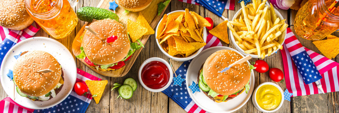 Celebrating Independence Day, July 4. Traditional American Memorial Day Patriotic Picnic with burgers,  french fries and snacks, Summer USA picnic and bbq concept, Old wooden background