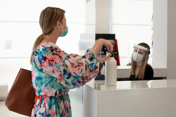 cliente vestita con un vestito a fiori si disinfetta le mani con un igienizzante gel per le mani...