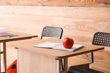 Modern school desks near wooden wall