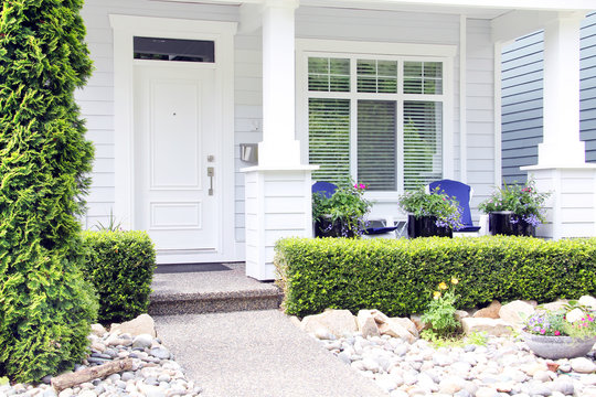 Beautiful new contemporary white home in a Canadian neighbourhood. Front door with a pretty porch and rock garden.