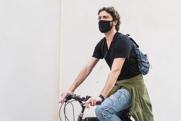 the midsection of a twenty-year-old boy rides a bicycle through the streets of the city wearing a safety mask due to coronavirus.  Urban lifestyle shot.