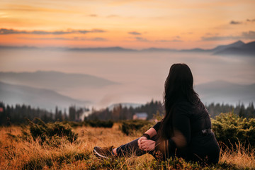Printed roller blinds Black a woman sits on top of a mountain waiting for the sun to rise. Mountains in the fog, the sky is orange, yellow grass. Meditation. The balance of life. Appeasement. Peace and joy in the soul. Tourism.