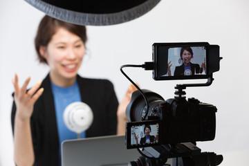 一眼レフカメラで動画を撮影する女性