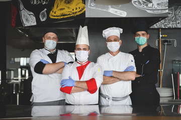 group chefs standing together in the kitchen at restaurant wearing protective medical mask and...