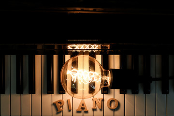 High Angle View Of Illuminated Light Bulb With Text On Piano - fototapety na wymiar