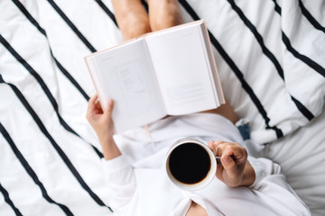 Top view image of a woman reading book and drinking hot coffee in a white cozy bed at home in the...