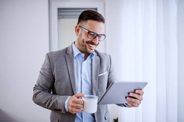 Attractive handsome classy caucasian smiling businessman in suit and with eyeglasses using tablet and holding mug with coffee while standing next to window in his office.