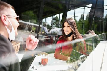 Papiers peints Echelle de hauteur couple with protective medical mask having coffee break in a restaurant