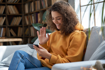 Happy young hispanic latin teen girl sit on sofa at home holding phone looking at screen waving hand video calling distance friend online in mobile chat app using smartphone videochat application.
