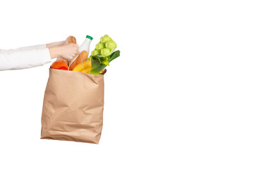 Female hands holds a paper bag filled with groceries isolated on white.