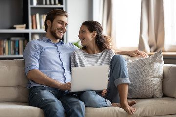 Happy young Caucasian couples it relax on couch in living room have fun browsing internet using...