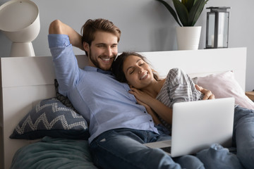 Happy young Caucasian couple lying relaxing in comfortable bed watching video on modern laptop, overjoyed millennial man and woman rest in cozy bedroom using computer together, technology concept