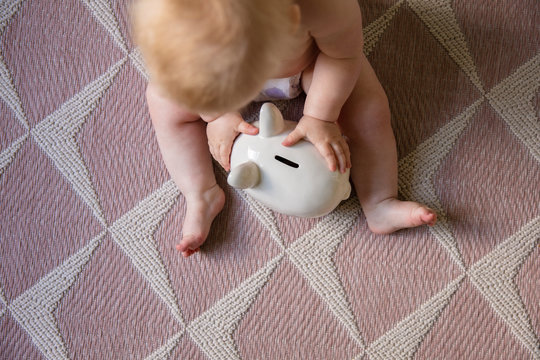 Baby starts saving early. overhead view of baby playing with a piggy bank