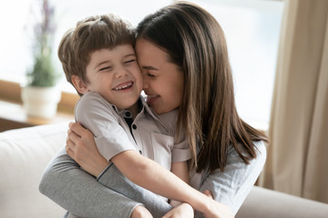 Happy young Caucasian mother hug cuddle cute little preschooler son enjoy tender time together at...