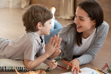 Overjoyed young mother and small preschooler son give high five playing drawing together, happy mom...