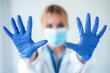 Portrait of female doctor with a medical mask showing hands to camera while wearing a blue nitrile...