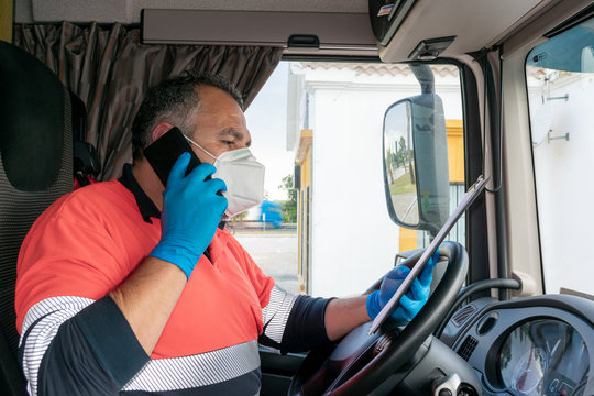 Truck driver with mask and gloves talking on the phone and reviewing documents.