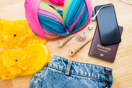 High Angle View Of Womenswear By Seashells With Mobile Phone And Passport On Table