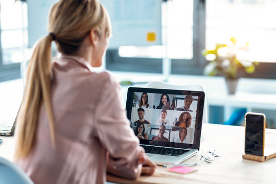 Female employee speaking on video call with diverse colleagues on online briefing with laptop at home.