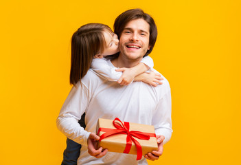 Little daughter kissing birthday father over yellow background