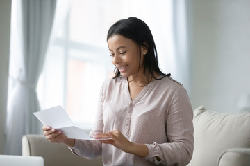 Young African woman sitting on sofa in living room reading postal letter feels happy. Getting bank lending approval notification or last payment loan document, student scholarship acceptance concept