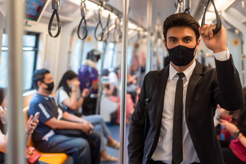 Portrait of confident businessman in black suit wear mask in city finding job during corona crisis using smartphone travelling by train