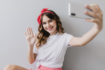 Wall Mural - Dreamy girl with wavy hairstyle posing with smile on light background. Indoor shot of wonderful young lady in white casual t-shirt making selfie.