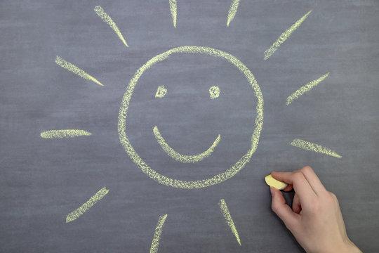 Cropped Hand Of Woman Drawing Sun On Blackboard