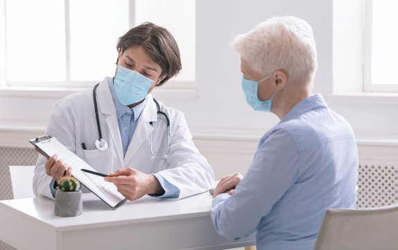 General practitioner showing analysis results to senior woman