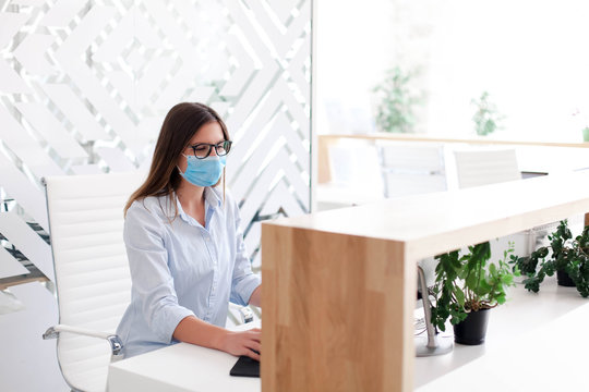 Receptionist wearing medical mask in office. Protection employees on workplace. Young woman working at reception in hotel. Disease prevention during quarantine, staff safety.