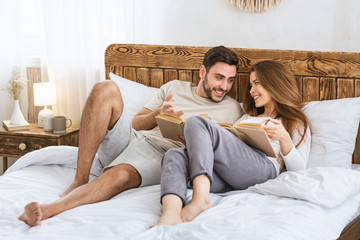 Couple reads books in bedroom. Guy and girl in home clothes on bed.