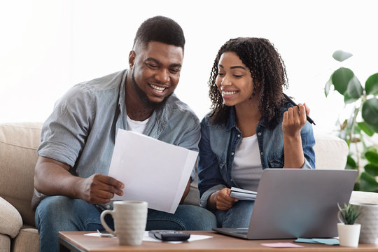 Black couple reading financial documentation at home while planning family budget