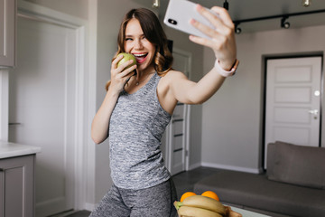 Wall Mural - Sporty girl taking picture of herself and smiling. Indoor photo of inspired lady eating apple and making selfie.