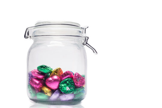 Close-up Of Wrapped Chocolates In Jar Against White Background