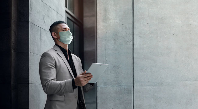 Covid-19 Situation in Business Concept. Businessman with Surgical Mask. Working on Digital Tablet. Stressed out due to Corona Virus. Looking away. Standing in the City