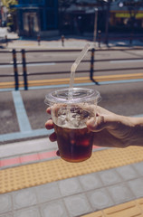 man holding plastic mug of iced convinience store coffee