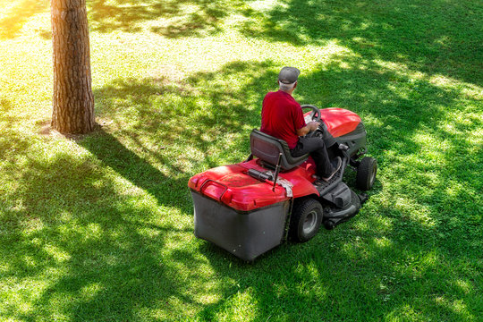 Top down above view of professional lawn mower worker cutting fresh green grass with landcaping tractor equipment machine at city park. Garden and backyard landscape lawnmower service and maintenance