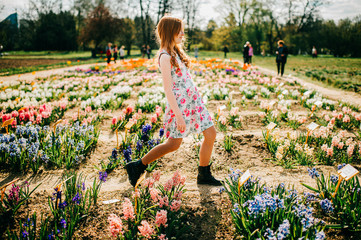 Cheerful young caucasian girl with long red hair and pale skin in flowers dress enjoys of the big flower garden