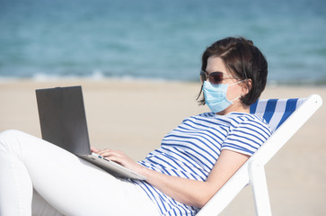 Young woman in a mask sitting with laptop on empty coast, protective equipment during coronavirus covid19. Social distance concept.