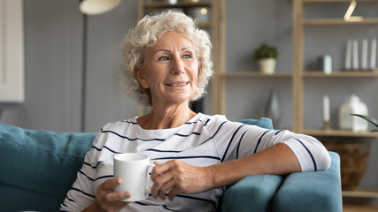 Head shot smiling old senior woman relaxing on comfortable couch with mug of hot tea, enjoying free...