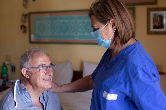 Infermiera con la mascherina facciale assiste anziano a domicilio seduto nel letto di casa sua che reagisce con un sorriso