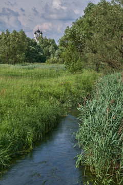 Summer landscape with a small river in the dense grass and an ancient Orthodox church in the distance. Moscow region, the village of Taininsky